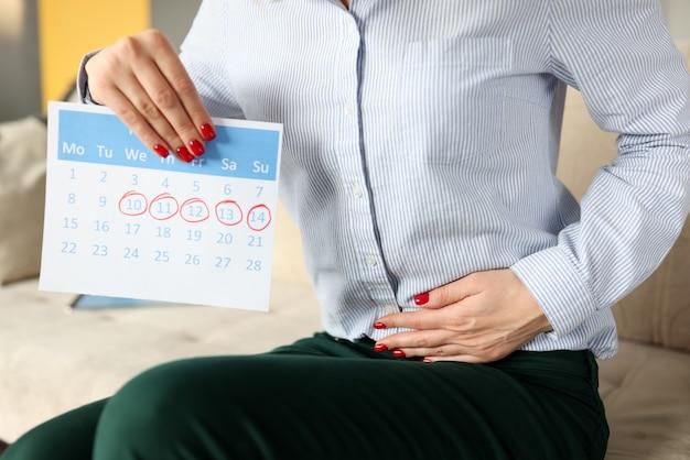 Kobieta siedzi na kanapie i trzymając się jej obolały brzuch zbliżenie. koncepcja cyklu miesiączkowego