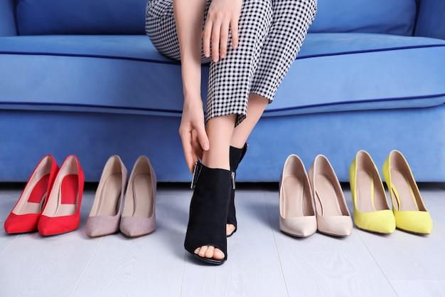 Kobieta siedzi na kanapie i wybiera buty w domu