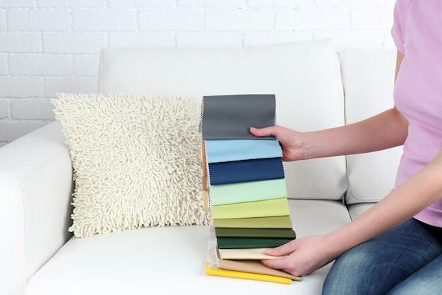Kobieta siedzi na kanapie i wybiera skrawki kolorowej tkanki