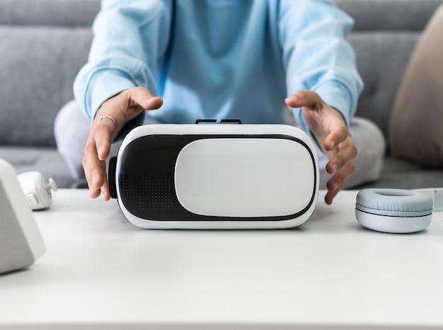 Kobieta siedzi na kanapie, podnosząc ze stołu okulary wirtualnej rzeczywistości
