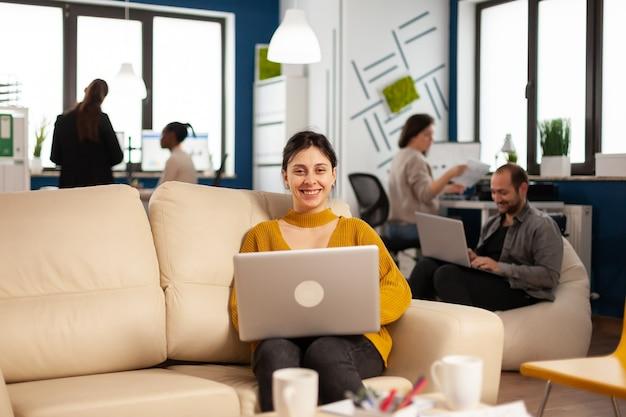 Kobieta siedzi na kanapie, trzymając laptopa, uśmiechając się do kamery, podczas gdy w tle pracują różni koledzy