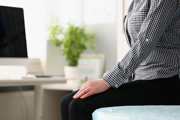 Kobieta siedzi na kanapie w biurze lekarza zbliżenie