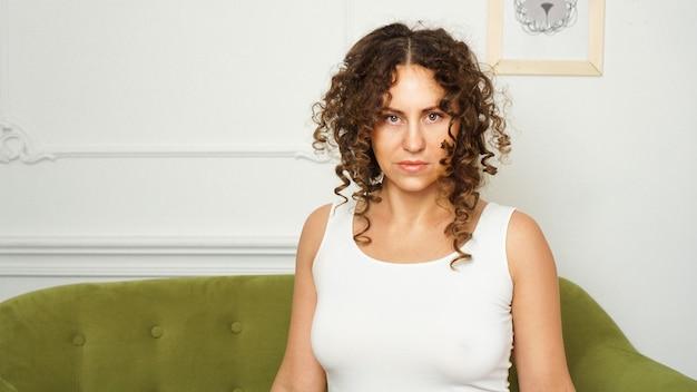 Kobieta siedzi na kanapie w salonie i patrząc w kamerę. poważne spojrzenie