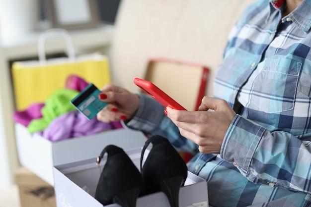 Kobieta siedzi na kanapie z pudełkiem butów i trzyma kartę bankową i smartfon