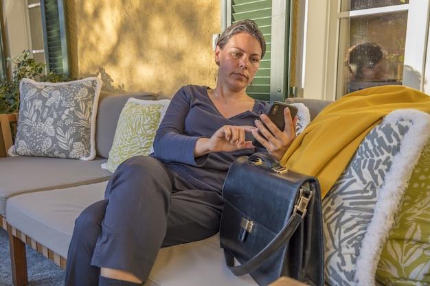 Kobieta siedzi na kanapie ze skrzyżowanymi nogami i przy użyciu smartfona w słońcu