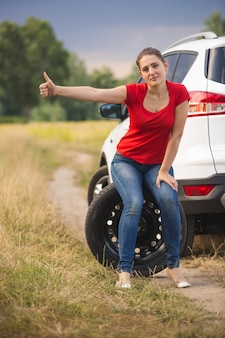 Kobieta siedzi na kole zapasowym w zepsutym samochodzie i jedzie autostopem