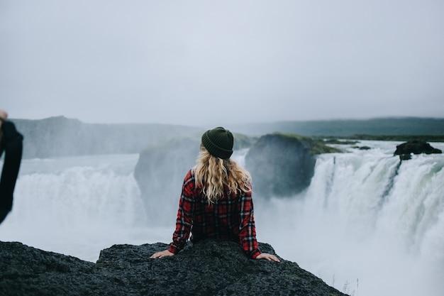 Kobieta siedzi na krawędzi urwiska nad wodospadem