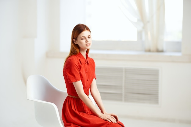 Kobieta siedzi na krześle czerwona sukienka pozowanie pokoju. zdjęcie wysokiej jakości