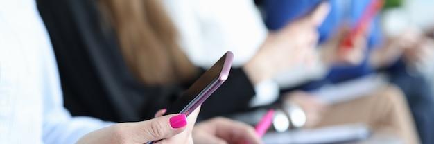 Kobieta siedzi na krześle i trzyma telefon w dłoniach na tle zbliżenia kolegów