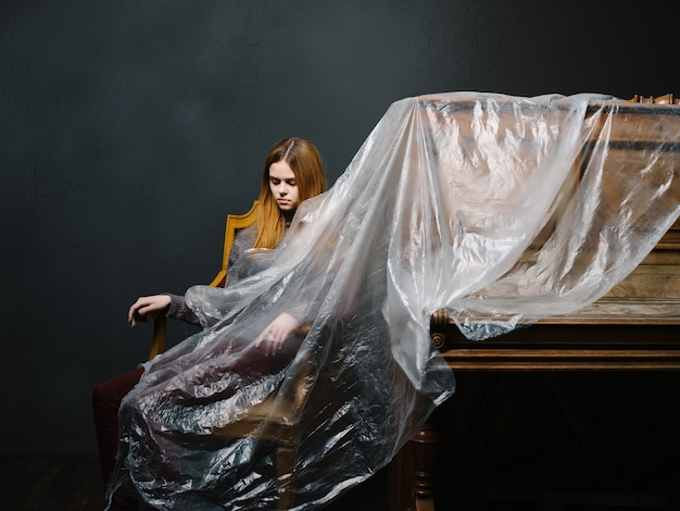 Kobieta siedzi na krześle obok ciemnego polietylenu fortepianowego tła