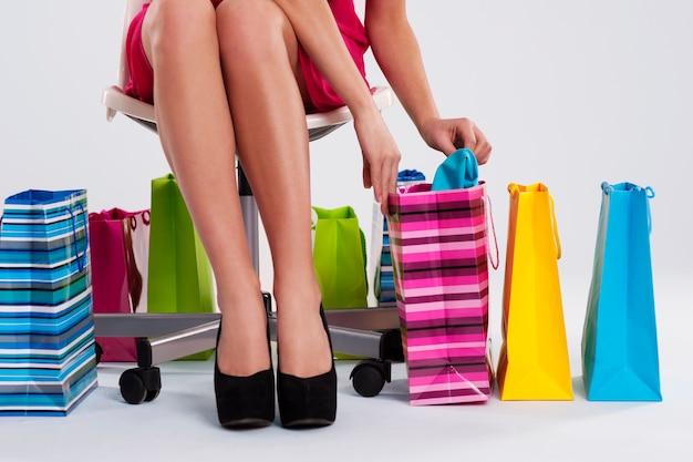 Kobieta siedzi na krześle obok toreb na zakupy