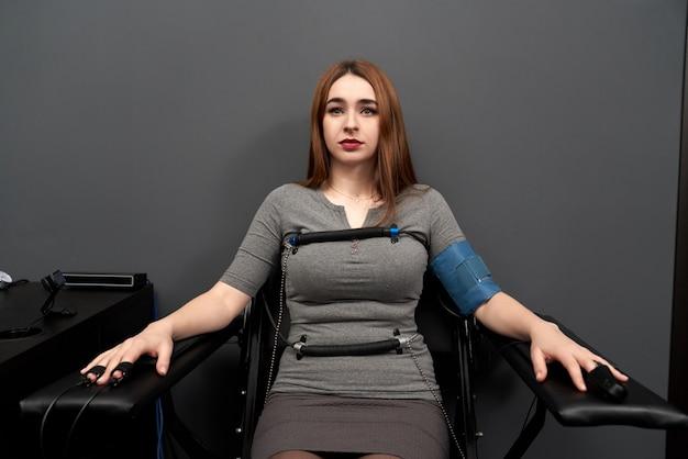 Kobieta siedzi na krześle podczas testu wykrywacza kłamstw