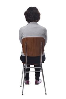 Kobieta siedzi na krześle z plecami na białym tle