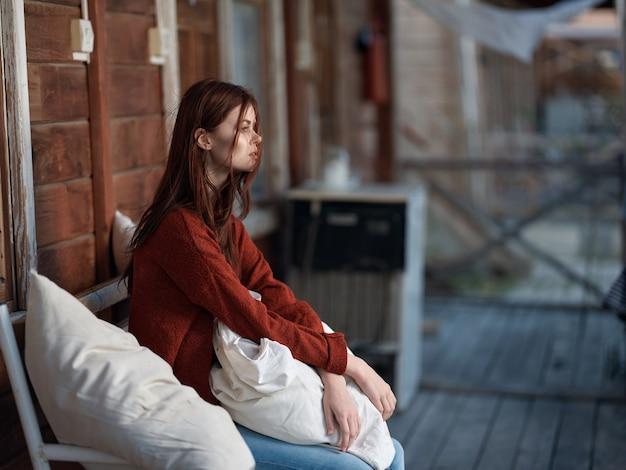 Kobieta siedzi na ławce w domu, moda