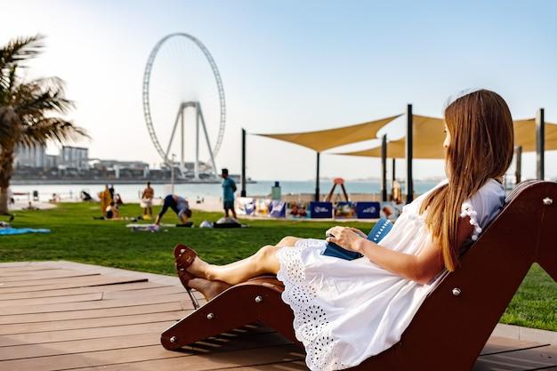 Kobieta siedzi na ławce w plaży jbr patrząc na koło oka dubaj