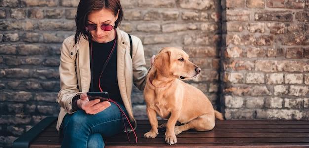 Kobieta siedzi na ławce z psem i przy użyciu telefonu