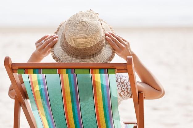 Kobieta siedzi na leżaku patrząc na morze