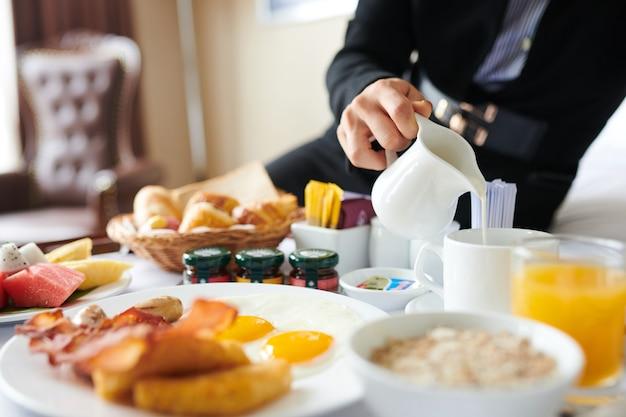 Kobieta siedzi na łóżku hotelowym i nalewa świeże mleko do filiżanki kawy podczas jedzenia smacznego śniadania