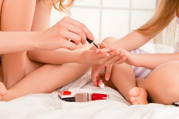 Kobieta siedzi na łóżku i maluje paznokcie córki