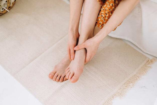 Kobieta siedzi na łóżku i masuje stopę