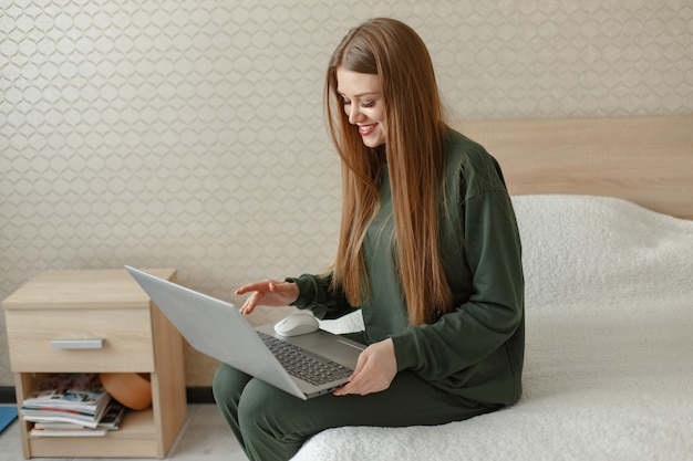 Kobieta siedzi na łóżku i używa laptopa