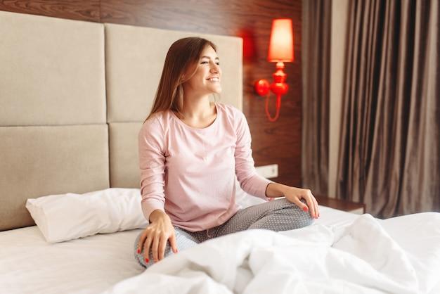 Kobieta siedzi na łóżku w pozie jogi, rano