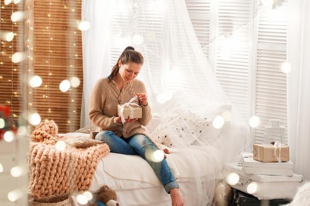 Kobieta siedzi na łóżku w przytulnym pokoju
