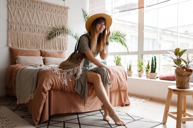 Kobieta siedzi na łóżku w swoim mieszkaniu boho