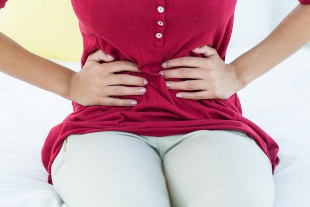 Kobieta siedzi na łóżku z bólem brzucha