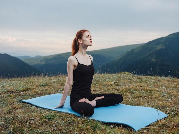 Kobieta siedzi na macie asana medytacja joga natura świeże powietrze. wysokiej jakości zdjęcie