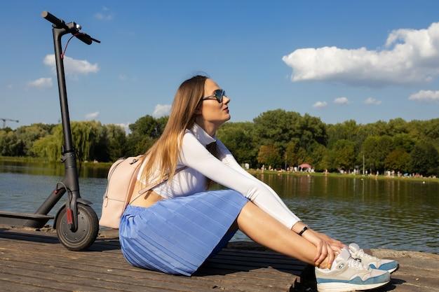 Kobieta siedzi na molo i cieszy się przyrodą w pobliżu ekologiczny skuter elektryczny