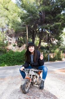 Kobieta siedzi na motocyklu i pokazuje znak zwycięstwa