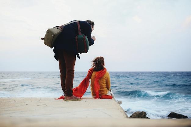 Kobieta siedzi na nabrzeżu, a mężczyzna robi jej zdjęcie