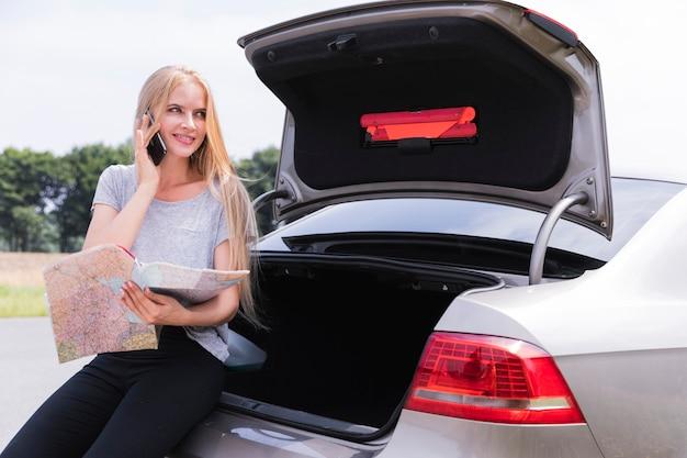 Kobieta siedzi na otwartym bagażniku samochodu