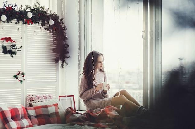 Kobieta siedzi na parapecie i pije kawę