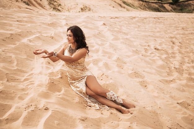 Kobieta siedzi na piasku pustyni i trzyma w ręku rozrzucanie piasku.