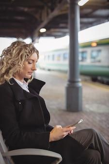 Kobieta siedzi na platformie przy użyciu telefonu komórkowego