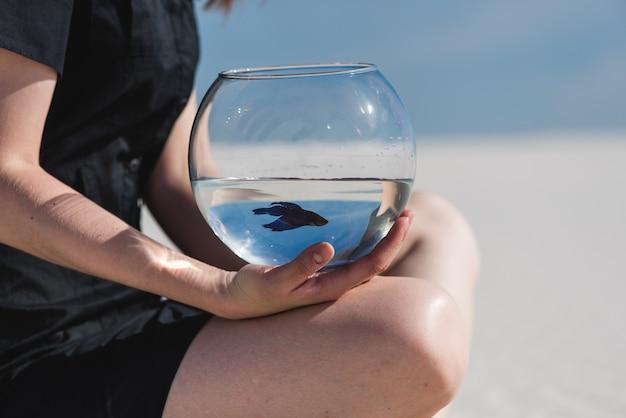 Kobieta siedzi na plaży z akwarium. tło pustyni lub piasku.