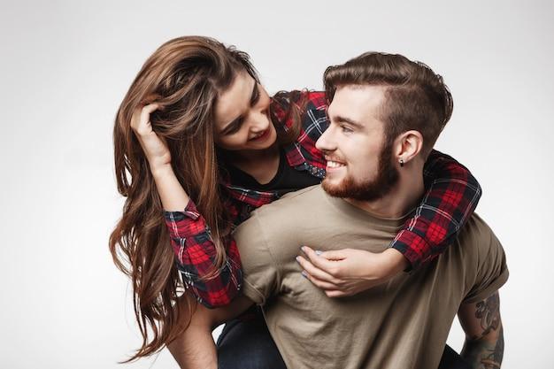 Kobieta siedzi na plecach mężczyzny zabawy, patrząc na niego.