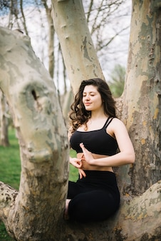 Kobieta siedzi na pniu drzewa medytacji gestem mudra