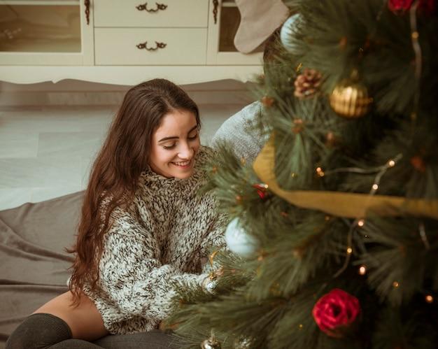 Kobieta siedzi na podłodze i dekorowanie choinki