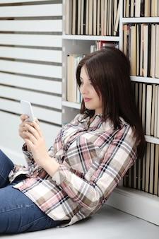 Kobieta siedzi na podłodze i maluje