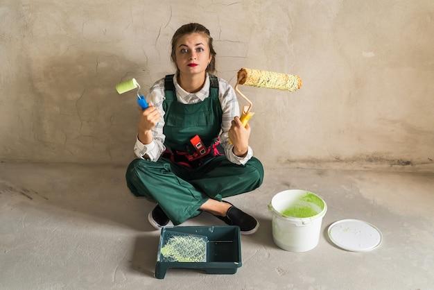 Kobieta siedzi na podłodze i pozuje z narzędziami do malowania