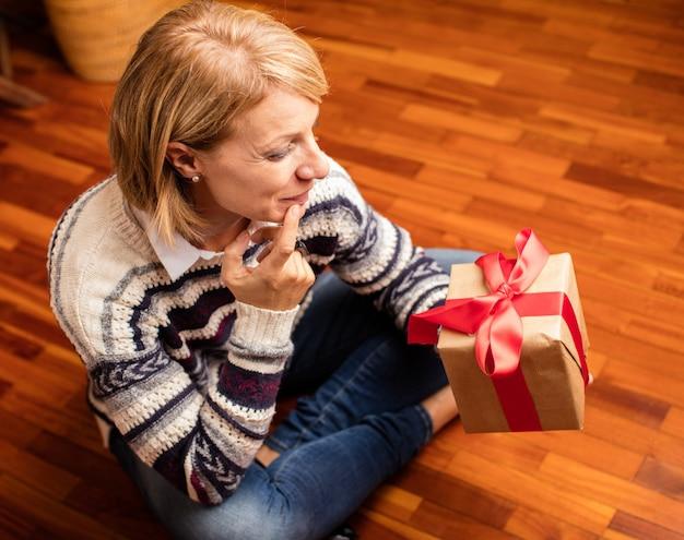 Kobieta siedzi na podłodze patrząc na prezent