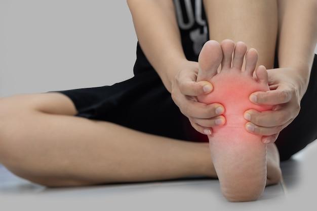 Kobieta siedzi na podłodze. ręka złapana na ból stóp
