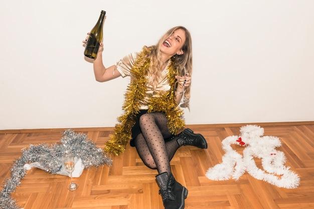 Kobieta siedzi na podłodze z butelką szampana