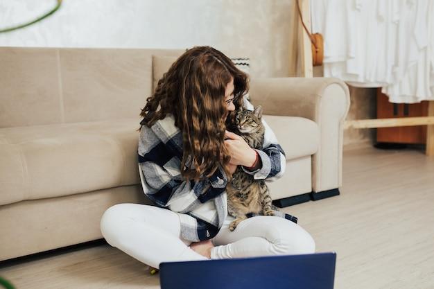 Kobieta siedzi na podłodze z laptopem i przytula kota