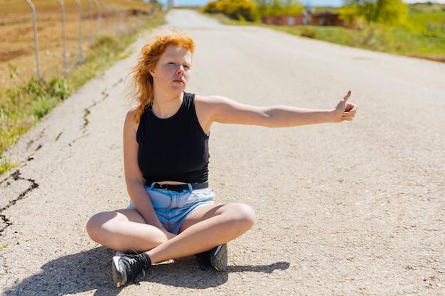 Kobieta siedzi na pustej drodze autostopem