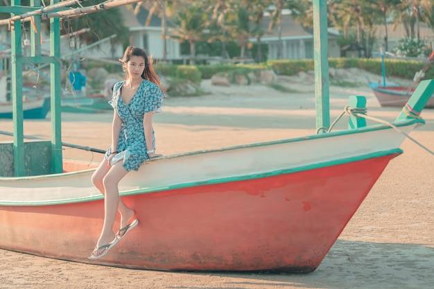 Kobieta siedzi na relaksującej plaży łodzi