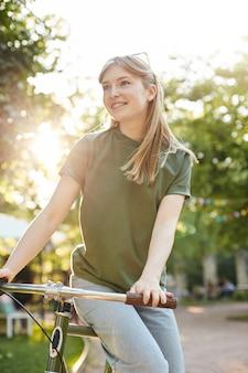 Kobieta siedzi na rowerze. portret młodej kobiety w parku miejskim, jazda na rowerze